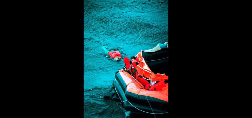 En ytbärgare drar upp en flytväst från vattnet efter att ha sökt igenom en gummiflotte.  Foto: Leif R Johansson/Pica Pressfoto