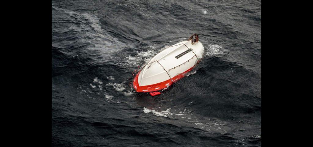 En livbåt som flyter upp och ner i det stormiga vattnet.   Foto: TT